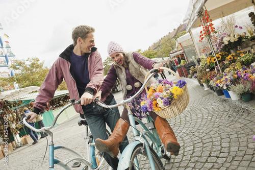 Deutschland, Bayern, München, Viktualienmarkt, Paar mit Fahrrädern, lachen, Porträt