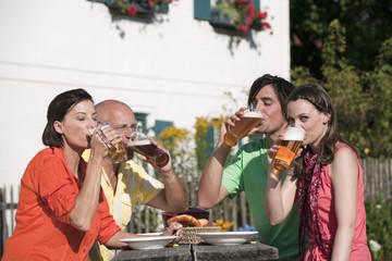 Deutschland, Bayern, Freunde trinken Bier im Garten