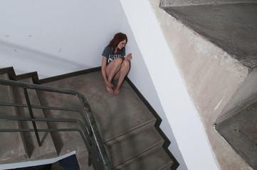 Nachdenkliche Frau sitzen gegen die Wand