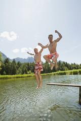 Italien, Südtirol, Männer springen in den See, kindisch