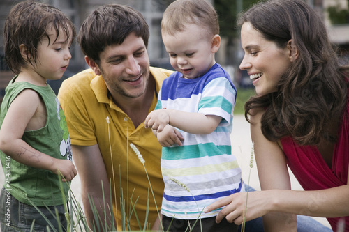germany, berlin, parents looking at ladybird on childs (2-3) arm, laughing, portrait