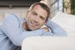 Deutschland, Mann sitzen Sofa, lächeln, Porträt