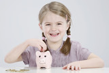 girl (4-5) putting coin into piggy bank, smiling, portrait