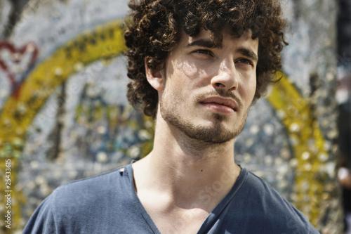 Deutschland, Berlin, Junger Mann vor Wand mit Graffiti, Portrait, close-up