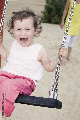 germany, berlin, girl (3-4) at playground, sitting on swing, laughing, portrait, close-up