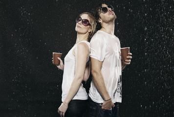 Mann und Frau stehen Rücken an Rücken im Regen