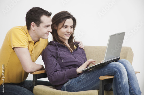 young couple using laptop, smiling.