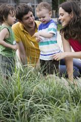 Deutschland, Eltern anschauen Marienkäfer Kind Arm, lachen, Porträt
