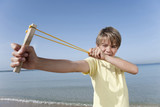 spain, mallorca, boy (8-9) using sling-shot