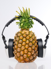 Pineapple with headphones on withe background
