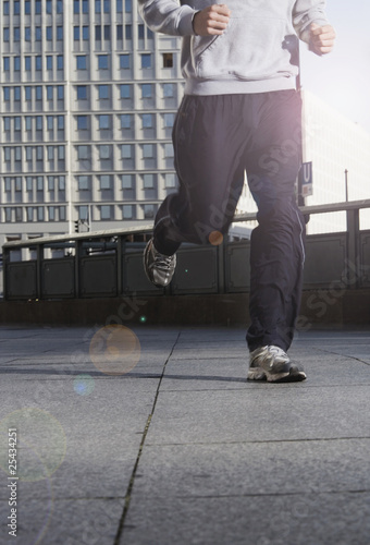germany, berlin, person jogging on street, skyscrapers in background, low section