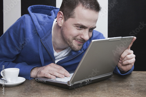 man staring at laptop, smiling