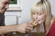 Deutschland, Junger Mann füttern Frau mit Brötchen, Portrait