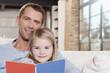 Deutschland, Vater und Tochter lesen Buch auf Sofa, Portrait, close-up