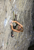 Female rock climber clinging to a cliff