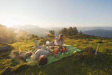 Junges Paar liegt auf einer Decke, mit Frühstück
