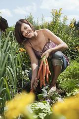 Deutschland, Bayern, Frau halten Bündel von Karotten im Garten, Lächeln, Portrait