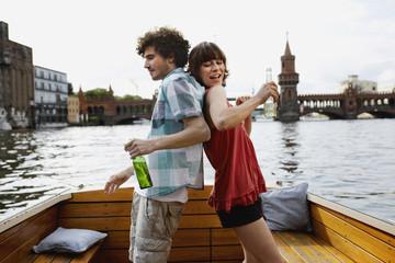 Deutschland, Berlin, Junges Paar auf dem Motorboot, mit Flaschen, Rücken an Rücken