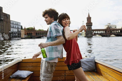 germany, berlin, young couple on motorboat, holding bottles, standing back to back
