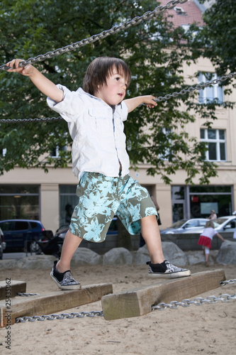 germany, berlin, boy (3-4) at playground on suspension bridge
