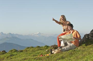 Junges Paar sitzt auf Berggipfel, Mann hält Karte, lächelnd