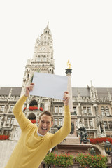 Deutschland, Bayern, München, Marienplatz, Mann halten leere Karte, Lächeln, Portrait