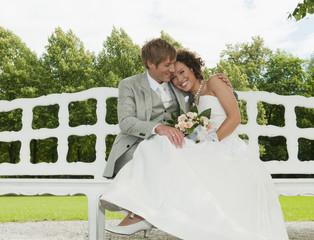 Deutschland, Bayern, Hochzeitspaar auf der Bank, im Freien, lächeln, Porträt