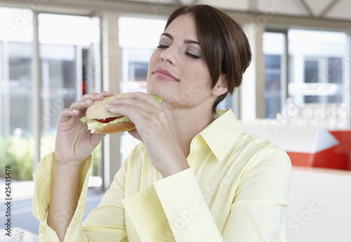 germany, cologne, businesswoman holding sandwich, eyes closed, portrait