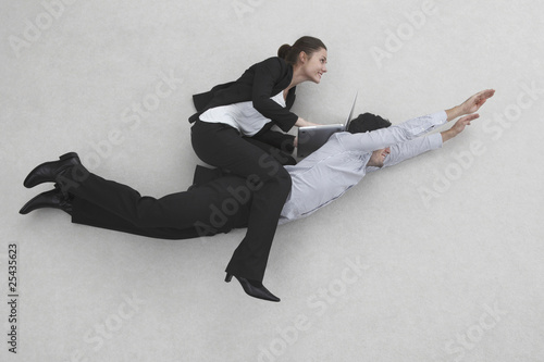 two businesss people, woman riding on man's back, side view, elevated view, portrait