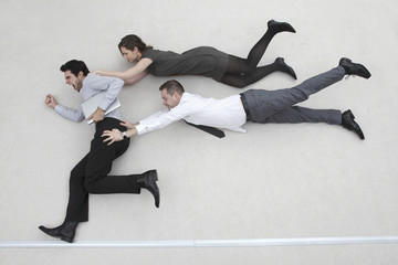 Geschäftsmann auf der Flucht, zwei Kollegen hinter ihm, in die Luft fliegen