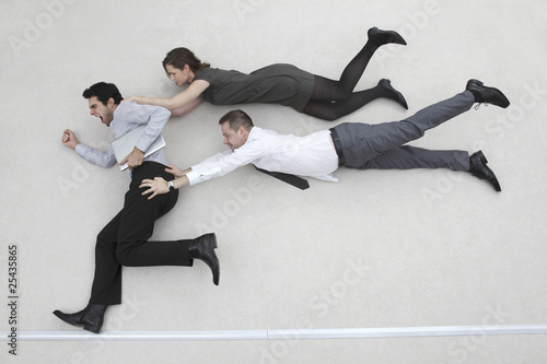 businessman on the run, two colleagues after him, flying in the air, side view