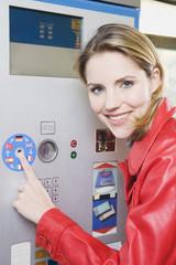 Deutschland, Bayern, München, Frau jung am Fahrkartenautomaten in U-Bahnstation, Lächeln, Portrait, close-up