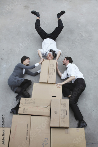 three business people on cardboard boxes, man doing handstand, smiling, portrait, elevated view