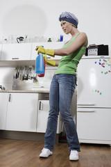 Deutschland, Frau jung in der Küche mit Sprühflaschen, Portrait