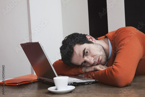 tired man with coffee cup and laptop