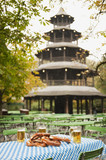germany, bavaria, english garden, beer mugs and pretzel on table, chinese tower in background