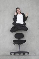Geschäftsfrau mit Handy, schwebt über Stuhl