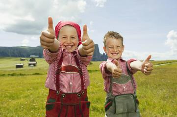 Italien, Seiseralm, Junge und Mädchen im Feld, Daumen nach oben, lächeln, Portrait, close-up