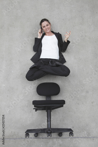 businesswoman using mobile phone floating above chair, elevated view