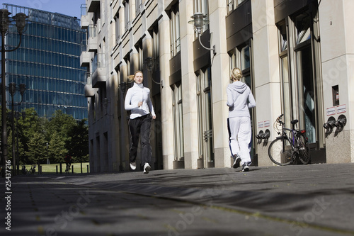 germany, berlin, two women jogging on street