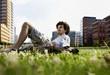 Deutschland, Berlin, Mann entspannen auf dem Rasen, Hochhäuser