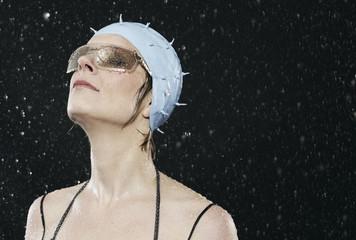 Frau mit Sonnenbrille steht im Regen