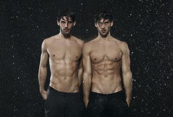Zwei Männer stehen im Regen, Wetter, die Hände in den Taschen, freier Oberkörper, nackt