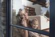 Deutschland, Mutter und Tochter sitzen am Fenster, Mutter mit Handy, Portrait