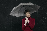 woman standing in rain, holding umbrella.