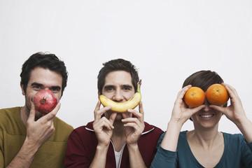 Männer und Frauen, die Früchte vor dem Gesicht