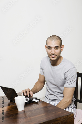 germany, berlin, young man using laptop