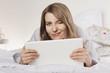 Frau liegt auf dem Bett mit Laptop, lächelnd