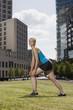 Deutschland, Berlin, Frau jung machen Dehnübungen auf Rasen