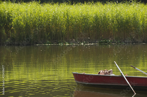 italy, south tyrol, young couple lying in rowing boat